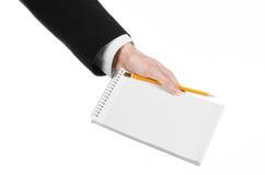 Affare ed argomento del reporter: la mano di un giornalista in un vestito nero che tiene un taccuino con una matita su un fondo b Fotografia Stock Libera da Diritti