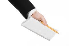 Affare ed argomento del reporter: la mano di un giornalista in un vestito nero che tiene un taccuino con una matita su un fondo b Immagini Stock