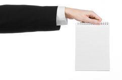Affare ed argomento del reporter: la mano di un giornalista in un vestito nero che tiene un taccuino con una matita su un isola b Immagini Stock Libere da Diritti