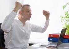 Affare emozionante che esamina computer portatile Immagini Stock