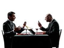 Affare facendo uso delle siluette della cena degli smartphones Fotografie Stock