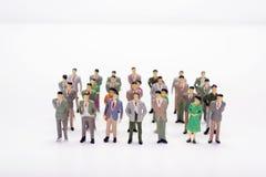 Affare miniatura della gente che sta nelle linee rette sopra bianco Fotografia Stock Libera da Diritti