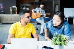 affare Multi-etnico Team Discussing Work in ufficio immagine stock