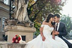 Affascinante amare appena la coppia sposata è abbracciante e sedentesi sulle fontane vicino al mazzo di nozze dei fiori rossi Immagini Stock Libere da Diritti
