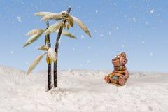 Affe betrachtet den Schnee, der vom Himmel nahe den schneebedeckten Palmen fällt Stockbilder