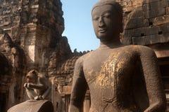 Affe, der auf altem Buddha sitzt Stockbilder