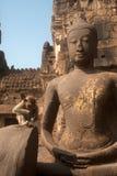 Affe, der auf altem Buddha sitzt Stockfotos