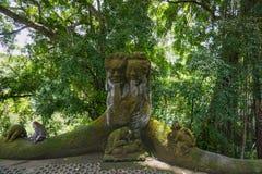 Affe, der auf einer Steinskulptur am heiligen Affewald in Ubud, Insel Bali, Indonesien sitzt lizenzfreie stockbilder