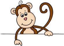 Affe, der unten über ein Zeichen zeigt Lizenzfreie Stockfotos