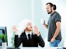 Affected narcissistic young businessman. Wearing a suit and white wig in the office , gesturing with his hands watched with disgust by a casual co-worker Royalty Free Stock Images