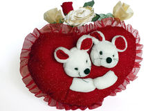 Affection. Valentine red heart-shaped pillow sham with teddy bears and artificial roses Royalty Free Stock Images