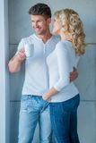 Affection couple standing looking out of a window Stock Photos