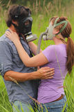 Affection in Dangerous Times. A loving affectionate couple with gas masks, standing in the tall grass. Allergies, bad breath or the apocalypse?  Shallow depth Royalty Free Stock Images
