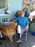 Affection for the dog. Senior is fondly talking the neighbors dog Royalty Free Stock Photography