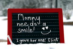 Affection from her son. Small child is perceptive to his moms need for some affection.  Chalk writing on red wooden slate that is sitting outdoors in snow Stock Photography