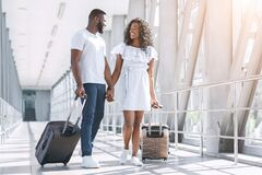 Free Affectionate Black Couple Enjoying Honeymoon Trip, Walking With Suitcases In Aiport Stock Image - 186267611