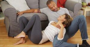 Affectionate black couple talking on floor Stock Photos