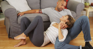 Affectionate black couple talking on floor. At home Royalty Free Stock Photos