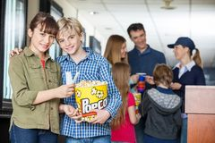 Affectionate Brother And Sister Holding Popcorn At Royalty Free Stock Images
