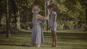 Caring mother comforting her sad daughter in park. Affectionate caucasian mother comforting her cute sad elementary age mixed race daughter in summer park stock video footage