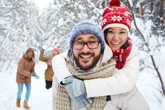 Affectionate couple. Amorous Asian couple on background of their friends playing snowballs on winter day Royalty Free Stock Photo