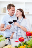 Affectionate couple drinking wine while cooking Stock Images