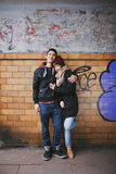 Affectionate couple embracing against a wall Stock Image