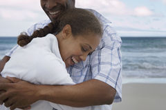 Affectionate couple embracing on beach at sunset, smiling, close-up Stock Image