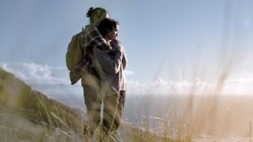 Affectionate couple embracing and looking away. Side view of affectionate couple embracing and looking away. Man and woman together on mountain looking at a sea stock video footage