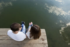 Affectionate couple fall in love. Affectionate couple sits on the mooring lake Royalty Free Stock Photo