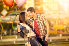 Affectionate couple having fun in amusement park. Laughing and looking at each other stock photo