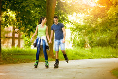Affectionate couple having leisure recreation. With rollerblades at park Stock Photo