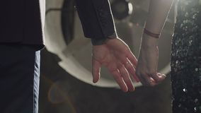 Affectionate couple holding hands outdoors. Close-up of affectionate reliable couple in trendy clothes holding hands expressing love, care, compassion and stock footage