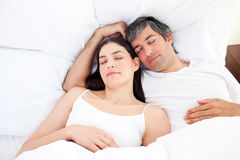 Affectionate couple hugging lying in their bed Stock Images