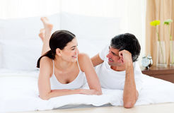 Affectionate couple interacting lying on their bed stock photography