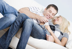 Affectionate Couple Laughing and Relaxing on Couch Royalty Free Stock Photos