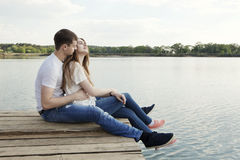 Affectionate couple at the nature. Affectionate couple sits on the mooring lake Royalty Free Stock Photos