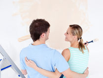 Affectionate couple painting a room. In their new house Stock Image