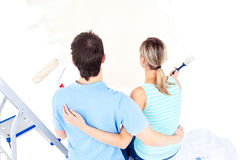 Affectionate couple painting a room. In their new house Royalty Free Stock Photos