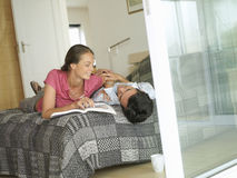 Affectionate couple relaxing on bed, woman reading magazine, smiling, view through doorway (tilt) Royalty Free Stock Photography