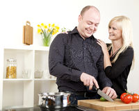 Affectionate couple preparing dinner Stock Photos