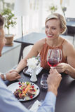 Affectionate couple toasting wine glass while having meal Stock Photos