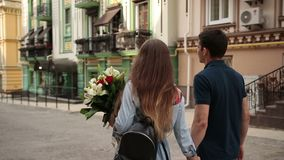 Affectionate couple walking down old city street stock footage