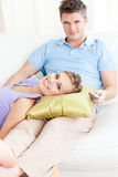 Affectionate couple watching television on sofa Royalty Free Stock Image