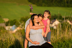 Affectionate daughters hugging happy pregnant mother outdoors. Young fit pregnant women with daughters on nature background Royalty Free Stock Images
