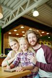 Cheerful family. Affectionate family relaxing in cafe at leisure or weekend stock images