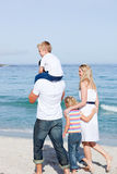 Affectionate family walking on the sand Stock Images