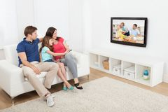 Affectionate family watching tv. Full length of affectionate family watching TV together at home Stock Photos