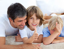 Affectionate father with his children having fun. Lying on a bed Royalty Free Stock Photo