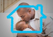 Affectionate father kissing his son on forehead. With digitally generated house outline royalty free stock image